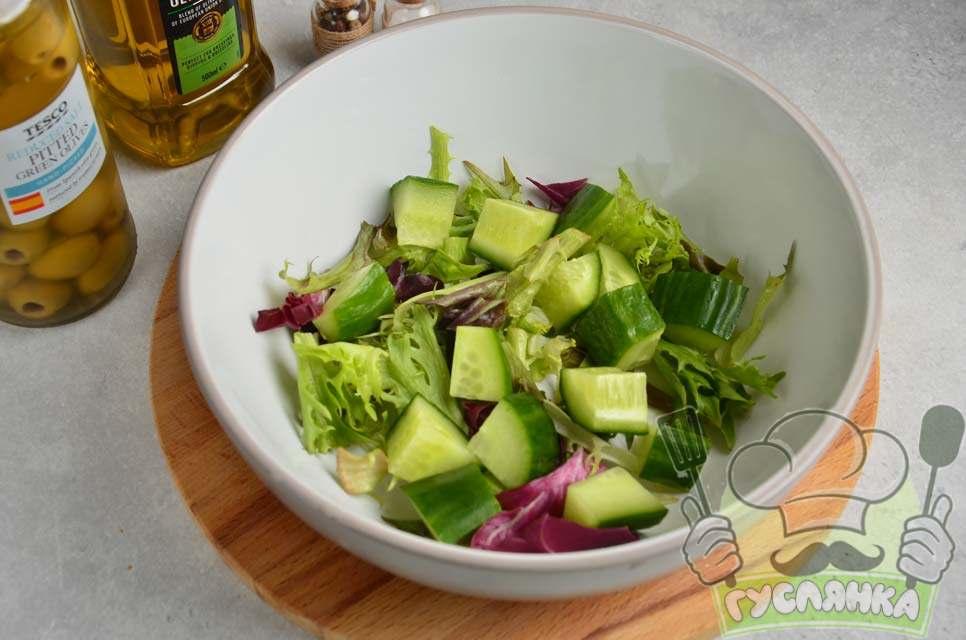 беру глибоку миску та кладу в неї мікс салат, свіжий огірок нарізаю кубиками і кладу до листя