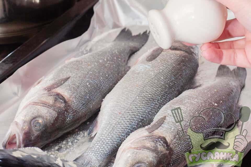 рибу перекладаю на деко, застелене фольгою, і солю сібасів з усіх боків і усередині