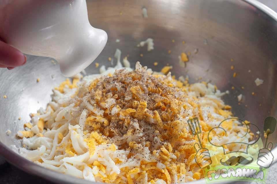 додаю до натертих яєць сіль, чорний мелений перець і натертий часник