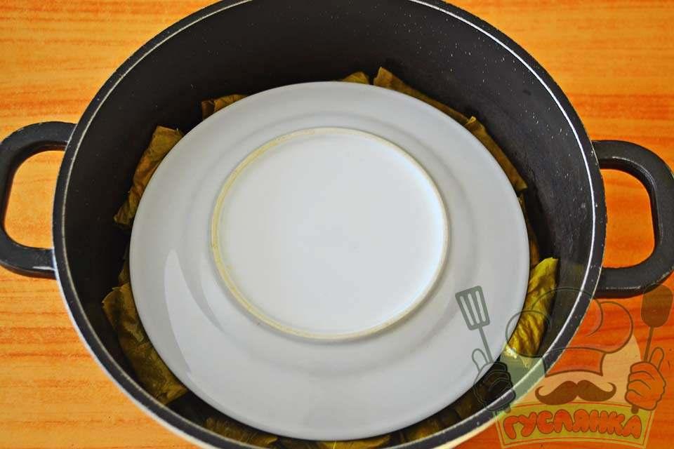 додаю трохи солі, накриваю тарілкою, трохи менше діаметром самої каструлі, заливаю рівно на два сантиметри вище тарілки окропом, варю, після закипання води, долму 40 хвилин на середньому вогні