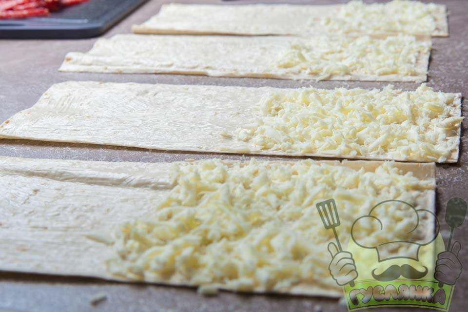з однієї сторони смужки викладаю натертий сир